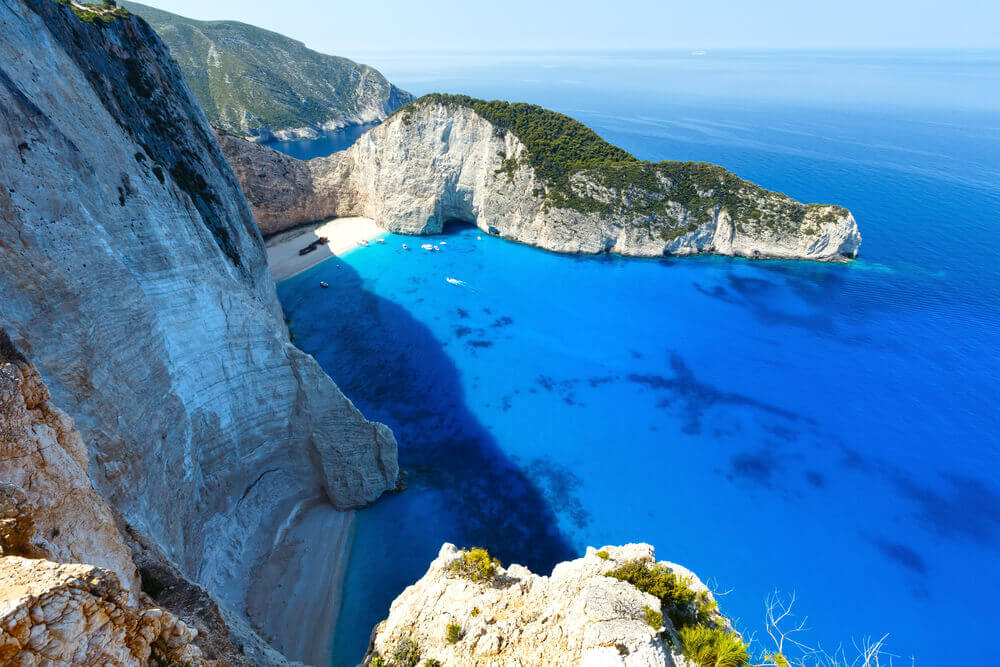 Top view of Shipwreck Cove (Navagio Beach), Zakynthos, Greece, bright blue sky, clear ocean, white cliffs , beach getaway