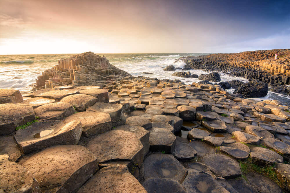Interlocking basalt columns look like puzzle pieces on the beach of Giant's Causeway, beach getaway