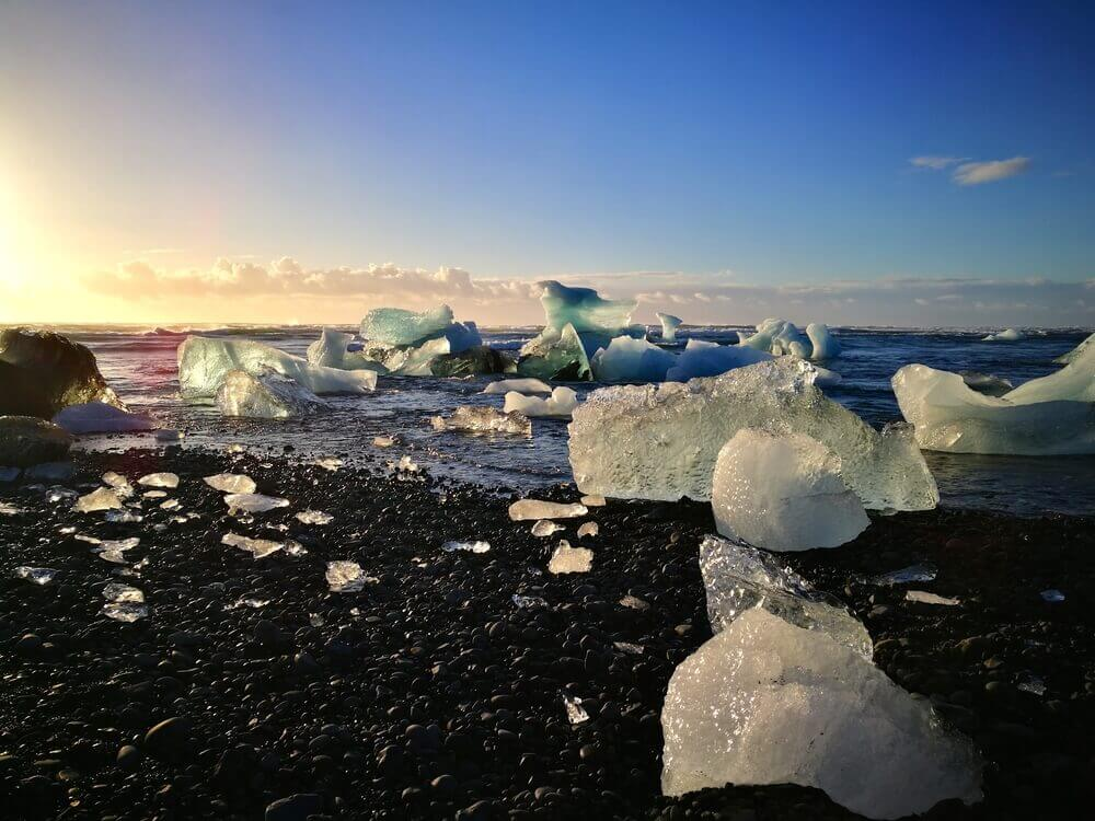 Chunks of fallen glacier lay on the dark sand of Jökulsárlón Lagoon, Iceland, beach getaway