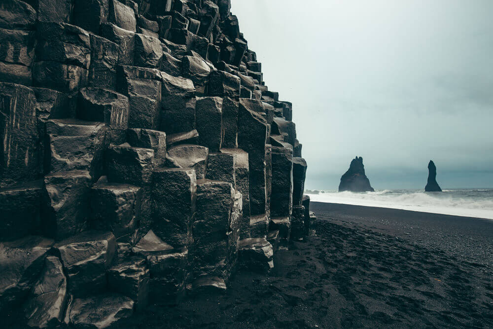 Dark stacks of basalt rocks on the black shores of Vik Beach, Iceland, beach getaway
