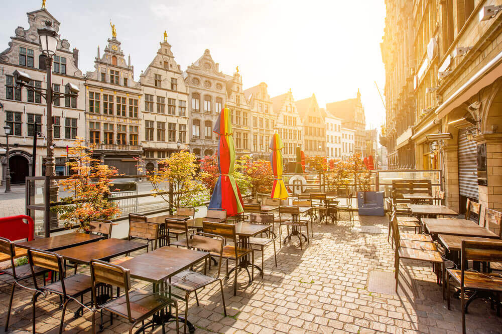 Holiday in Belgium: Sunrise at an empty cafe in a wide, old street in Antwerp