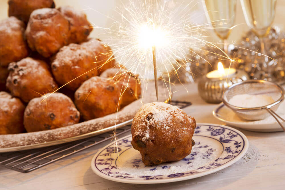 Holiday in Belgium: Oliebolen pastry on a plate with a sparkler, next to a big pile of other oliebolen