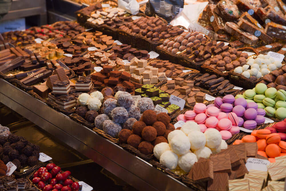 Holiday in Belgium: Extensive assortment of chocolate on display, next to colourful macaroons