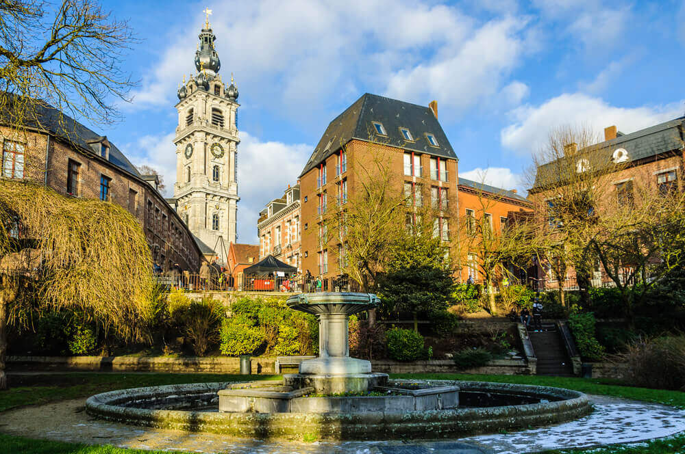 Holiday in Belgium: View of small, green public courtyard with stone fountain and old buildings in Mons
