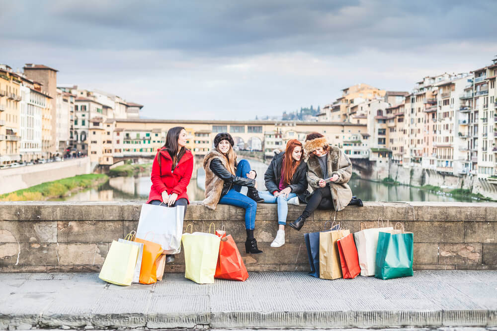 planning a trip to Italy. Four young female friends take a break from shopping for the city shops. Are sitting on the railing of a bridge, two talk while two look phone, shopping bags around them, behind them the Ponte Vecchio