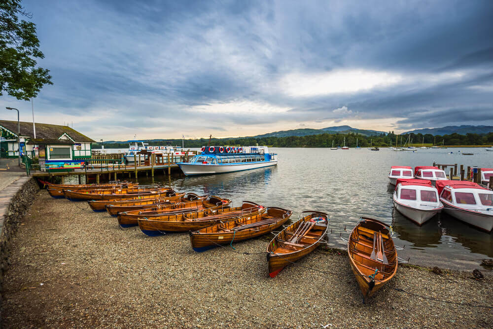 trip to England. Lake District, Cumbria - Traditional wooden boats and tourist boat at Derwentwater, Keswick at sunset with cloudy sky - England
