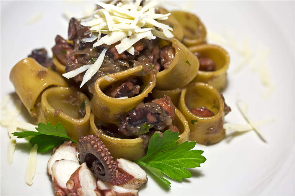 Pasta called calamarata with octopus and parsley. attractions in Italy