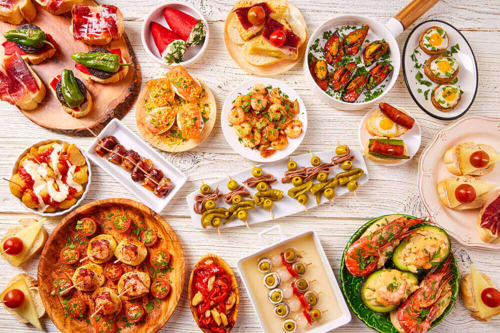 Tapas mix and pinchos food from Spain recipes also pintxos on a white wood board. Tapas In Spain