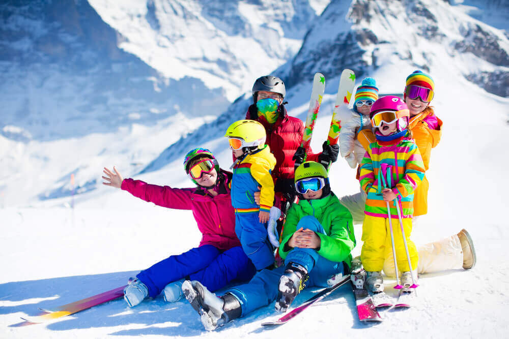 plan your trip. Family ski vacation. Group of skiers in Swiss Alps mountains.
