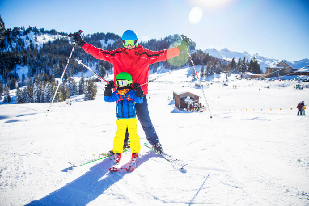 plan your trip. Kitzbuhel. Little boy having fun with his attractive father during skiing in Alps.