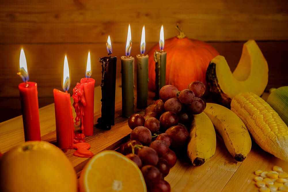 planning your trip. Kwanzaa holiday concept with decorate seven candles red, black and green, gift box, pumpkin,corn and fruit on wooden desk and background.
