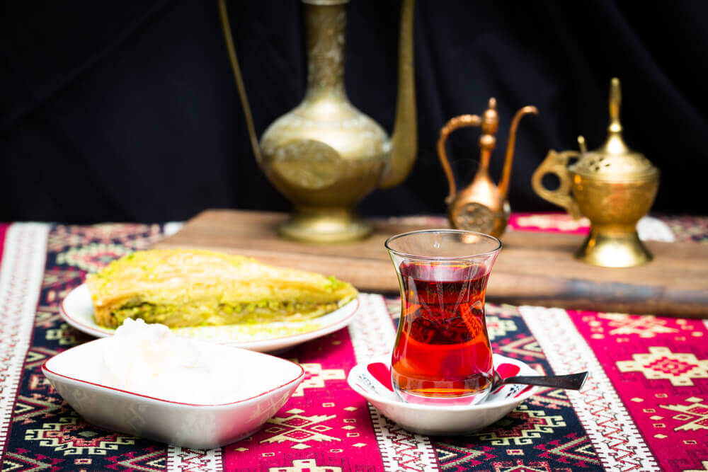 plan my route. Turkish baklawa with ice cream and pistachios and tea in pear shaped glass. Oriental style arrangement with vintage jars on ethnic table cloth, copy space still life