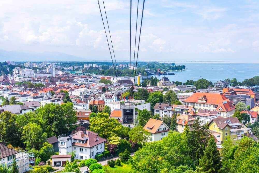 plan your trip. View of a pfanderbahn cable car with the Austrian city Bregenz behind it.