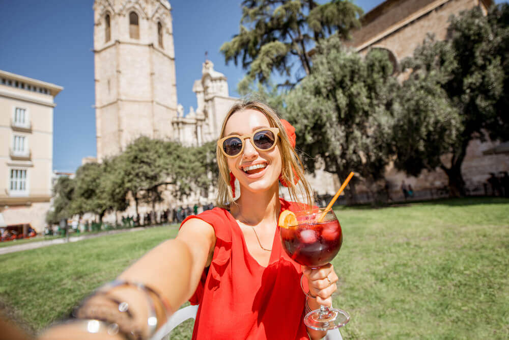 travel to europe. Young woman making selfie photo with sangria, traditional spanish alcohol drink, sitting outdoors in the old town of Valencia