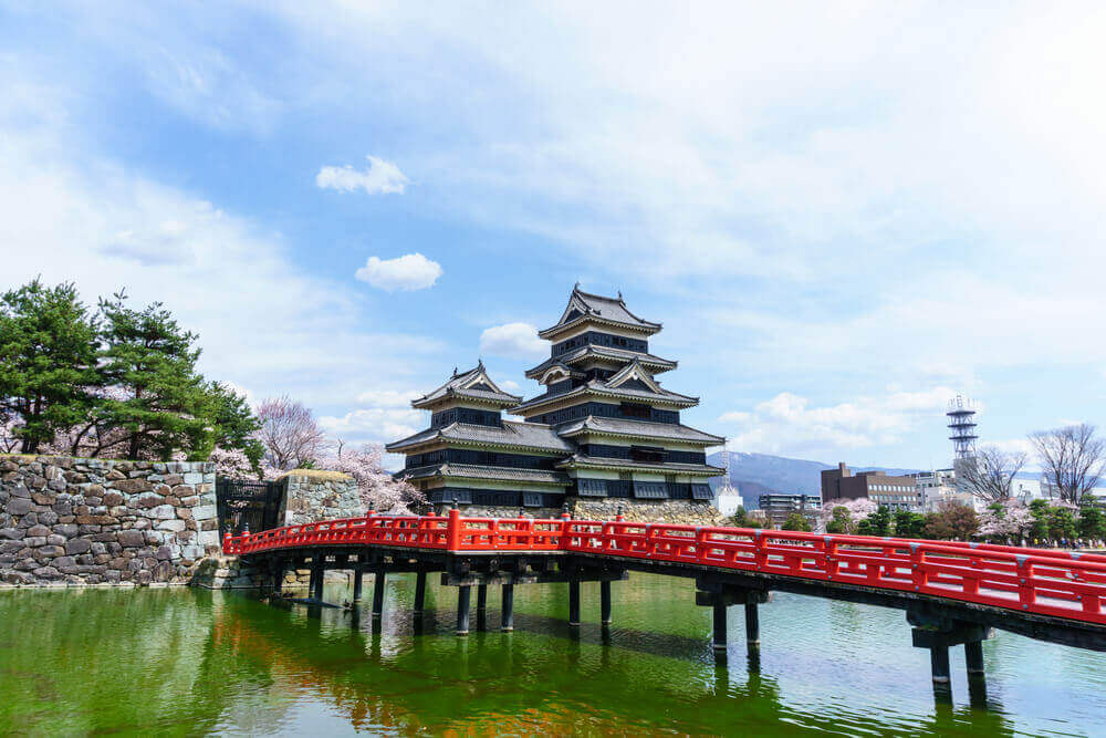 landscape view of Matsumoto Castle and red wooden bridge against blue sky and cloud. this castle symbol of japan ancient feudal historic culture in Nagano,Japan. touring plans