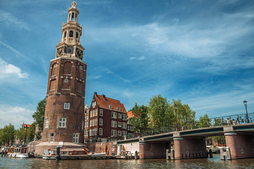 plan a trip to Europe. Old brick bell tower and bridge near the tree-lined canal with moored boats and blue sky in Amsterdam. Famous for its huge cultural activity, graceful canals and bridges. Northern Netherlands.