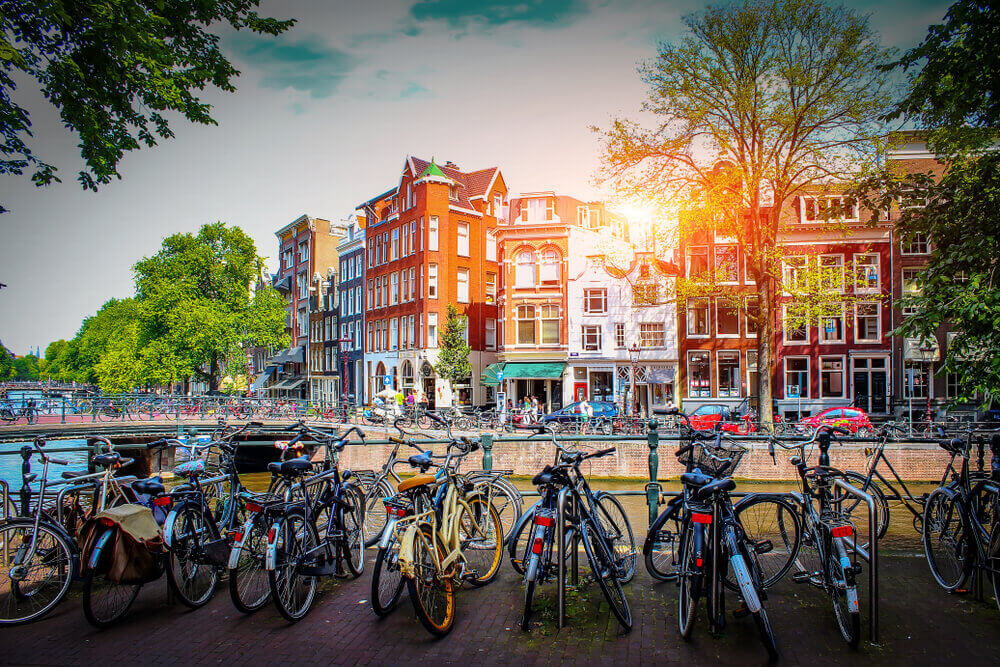 plan a trip to Europe. Parking for bicycles on background of old city at sunset in capital of Netherlands. Streets for walks in Amsterdam