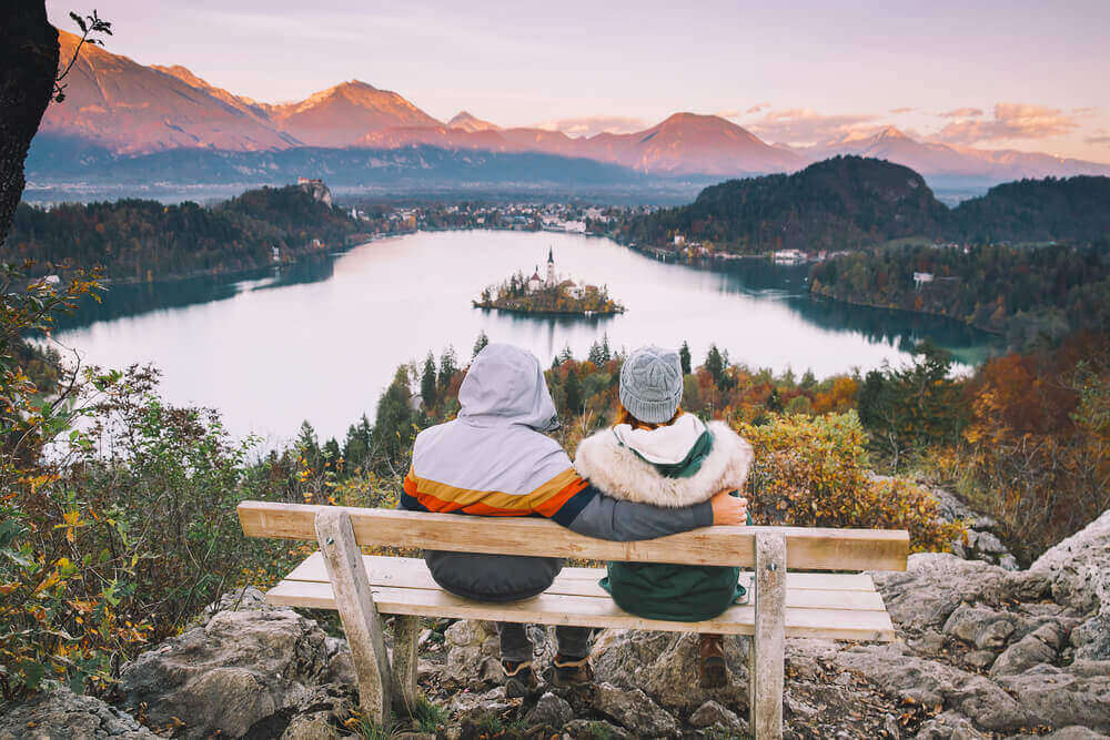 Couple in love looking on Bled Lake. Top view on Island with Catholic Church in Bled. European destinations