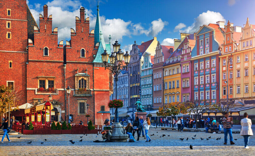 Wroclaw central market square with old colourful houses, street lamp and walking tourists people at evening sunset sunshine. European trip