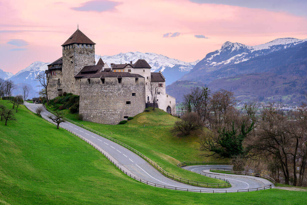 Vaduz Castle, the official residence of the Prince of Liechtenstein, with snow covered Alps mountains in background on sunset. vacation planner