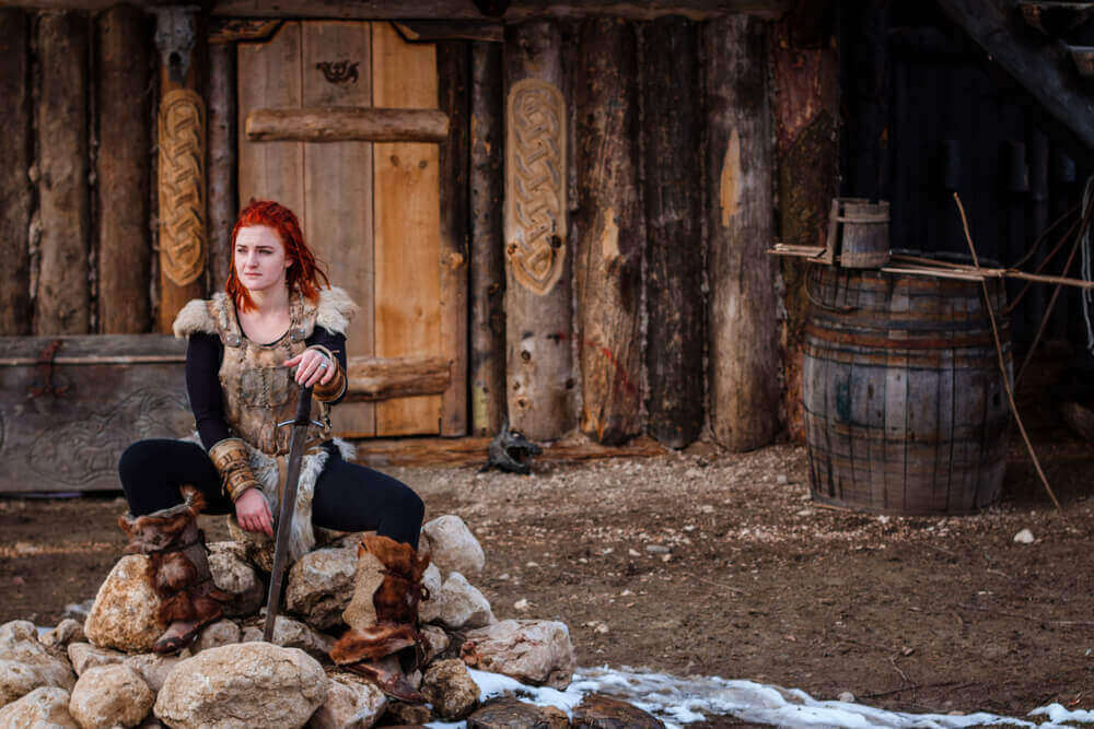 Red-haired woman is a Viking. Against the backdrop of a village or an ancient settlement. In the hands of a sword. viking tour
