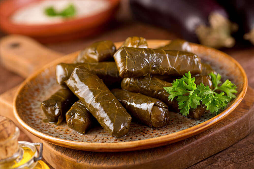 A plate of delicious stuffed grape leaves with parsley garnish. vegetarian holiday