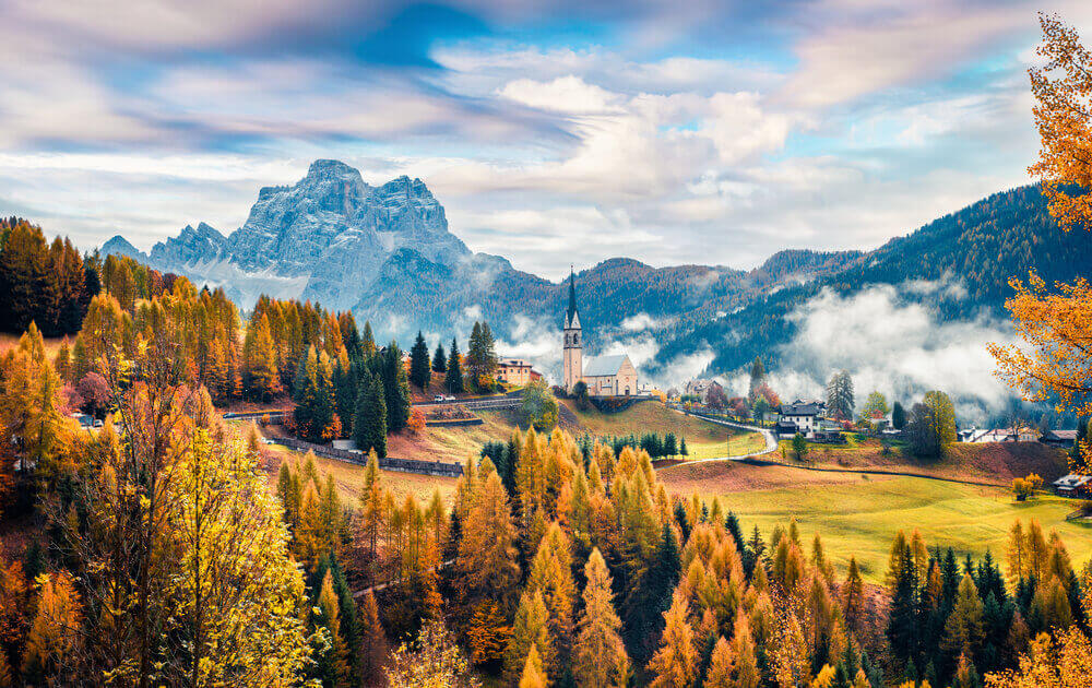 Foggy autumn view of Parrocchia Di Selva Cadore church. Great morning scene of Dolomite Alps, Cortina d'Ampezzo, southern Alps in the Veneto region of Northern Italy, Europe. Italy in September