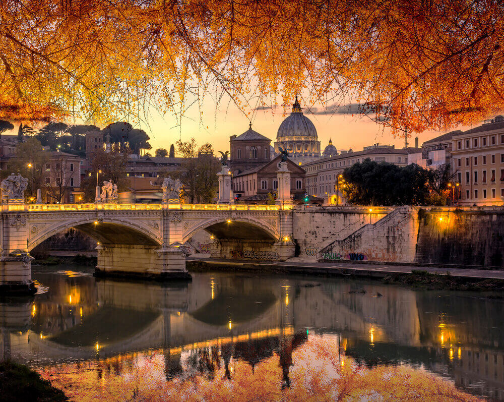 Rome and Vatican, cityscape at sunset with yellow, golden and orange autumn leaves, with St peter's basilica and bridge over the river Tiber. Italy in September