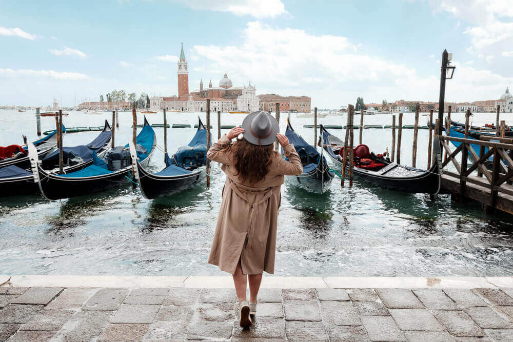Young woman in a hat on a background of water in Venice. Italy in September